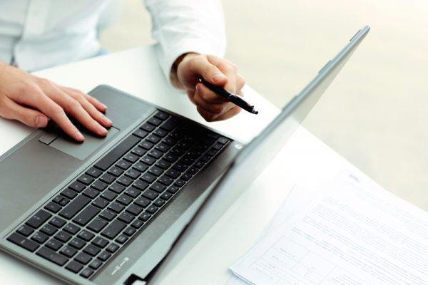 Closeup of bookkeeper using laptop