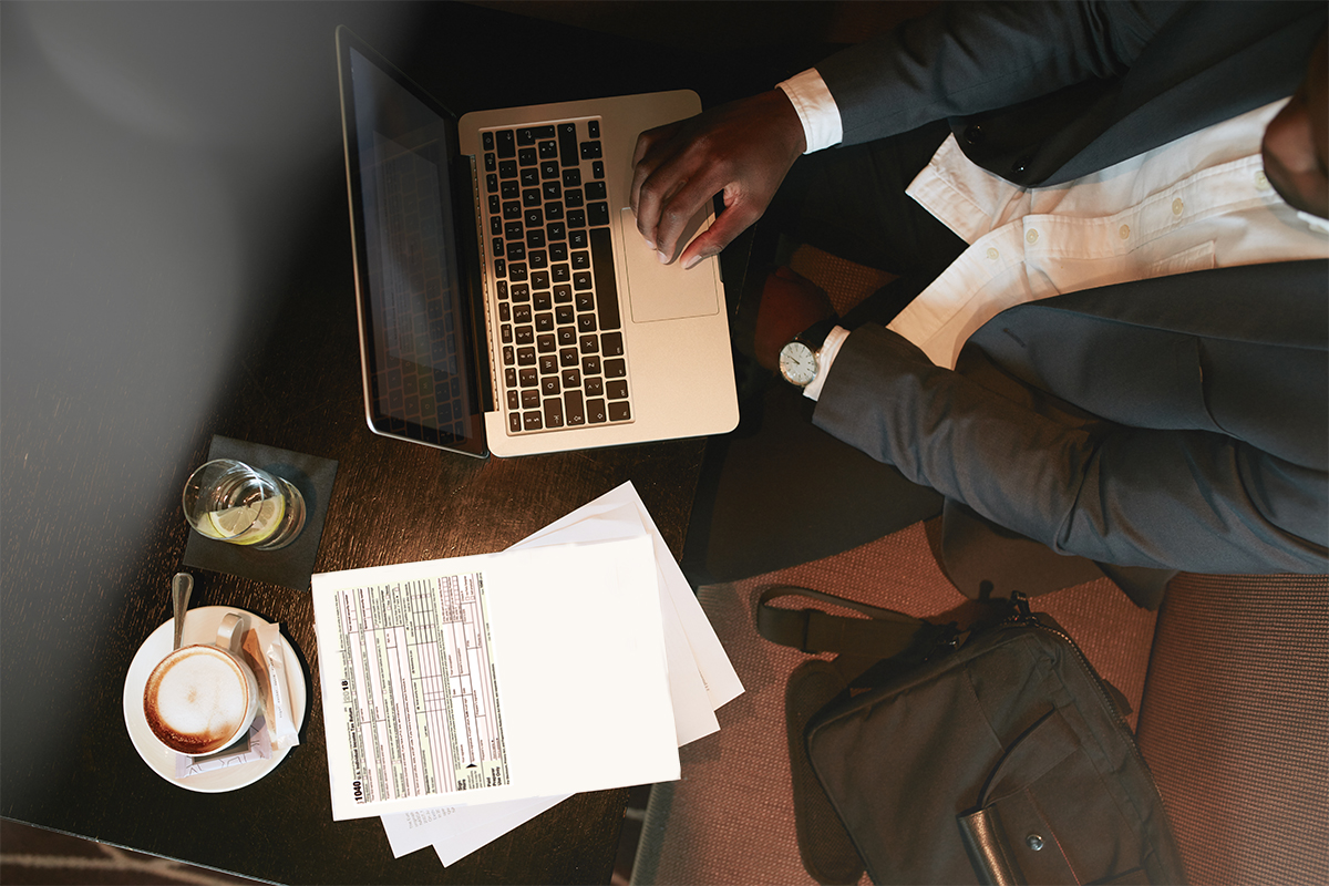 man in front of tax form on laptop