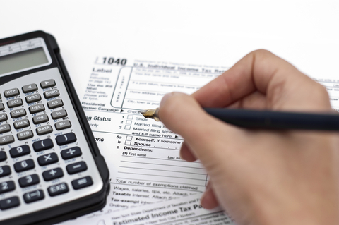 Hand filling out Tax Document and Calculator